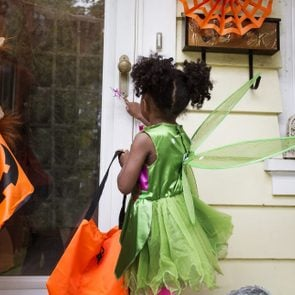 two children ringing doorbell while trick or treating on halloween