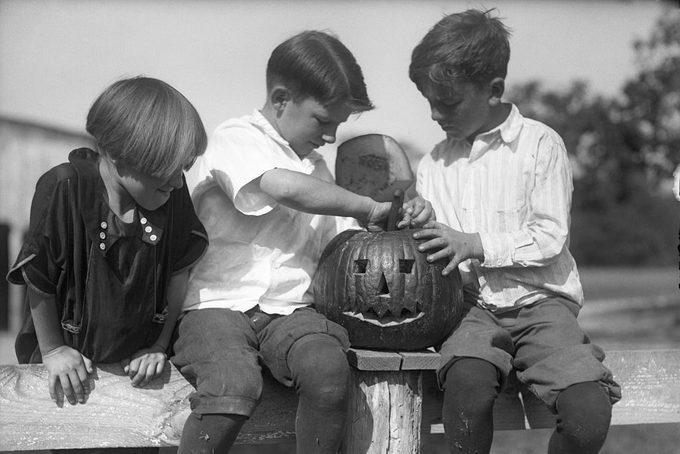 Children carving Jack O'lantern