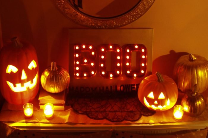 """Halloween Marquee Lights spell out """"BOO"""" and sits on a table surrounded by jack-o-lanterns, pumpkins, and candles"""