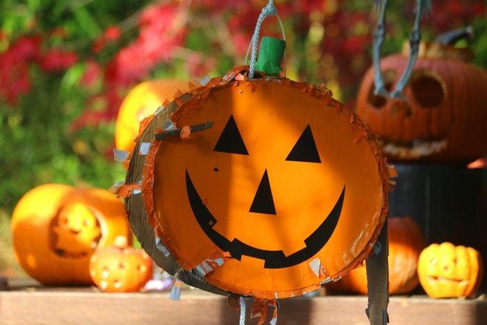 Halloween pumpkin pinata hanging at a party