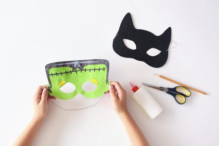 hands making paper halloween masks; cat and frankenstein masks