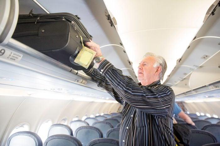 Senior man puts heavy luggage into plane's overhead compartment