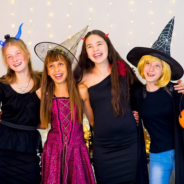 four smiling teen girls dressed in halloween costumes