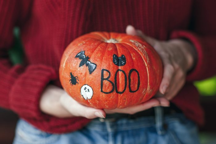 """Woman holding a pumpkin painted for halloween; pumpkin is painted with the letters """"BOO"""", a bat, spider, cat, and ghost"""