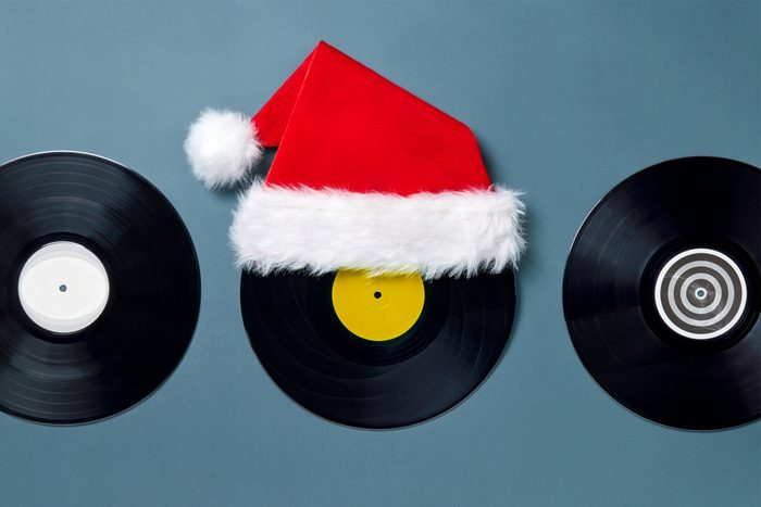 Flatlay of 3 vinyl records, the middle one has a Santa clause hat on top of it.