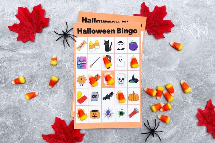 Halloween Bingo Card with candy corn, plastic spiders, and red autumn leaves on a gray textured background
