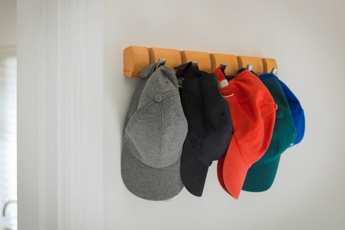 baseball hats hanging on hooks in home