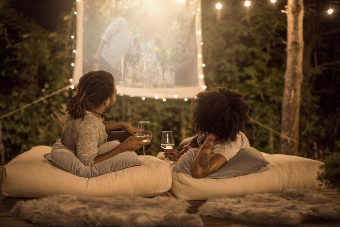 couple watching a movie outside in the backyard while drinking wine