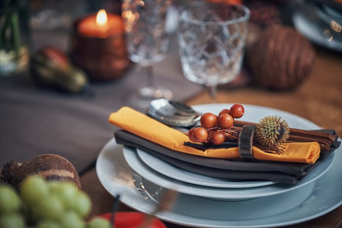 Decorated Table for Thanksgiving Dinner with Candles, Pumpkins, Leafs and Nuts