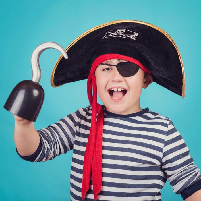 Portrait Of Happy Boy Wearing Pirate Costume While Standing Against Blue Background
