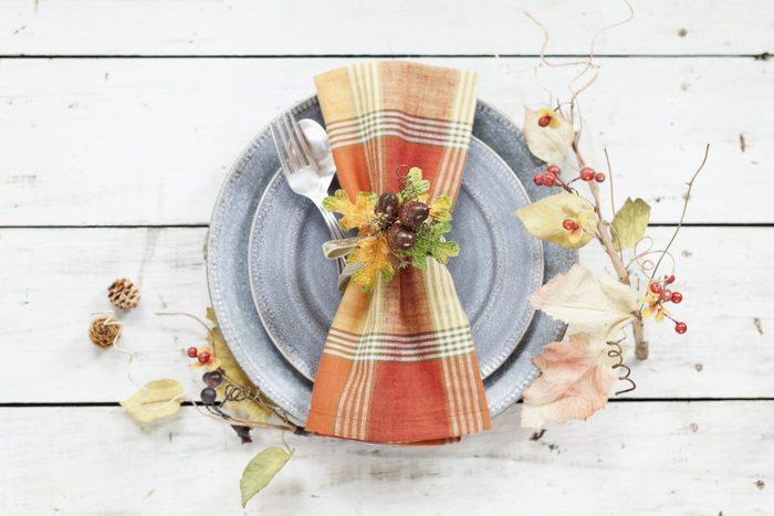 plain napkin on plate with leaf napkin ring