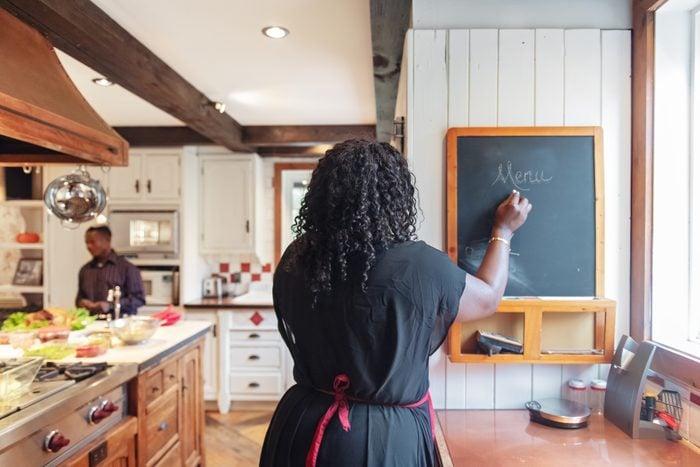 woman writing down menu on chalkboard in the kitchen