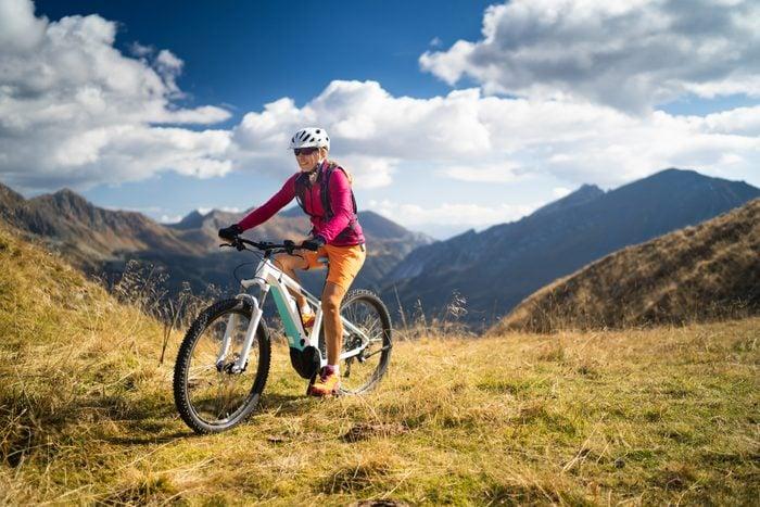 woman riding her bike through the mountains