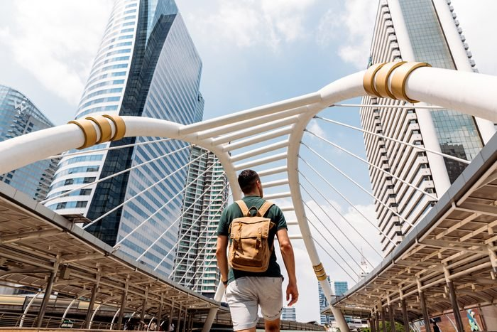 Rear view of a man with backpack admiring modern skyscrapers in Bangkok, Thailand