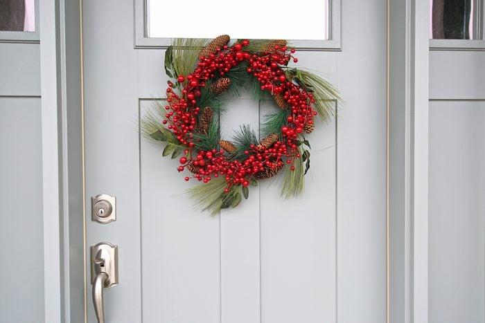 red berry wreath on front door of house