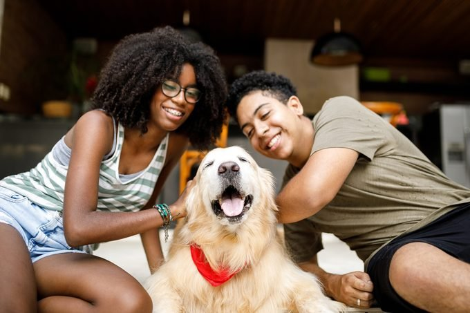 Two people smiling with their golden retriever dog