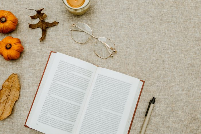 Flatlay of book and fall themed objects on speckled gray background