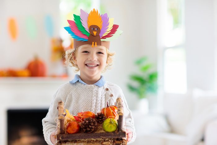 Child on Thanksgiving. Kid with autumn turkey hat.