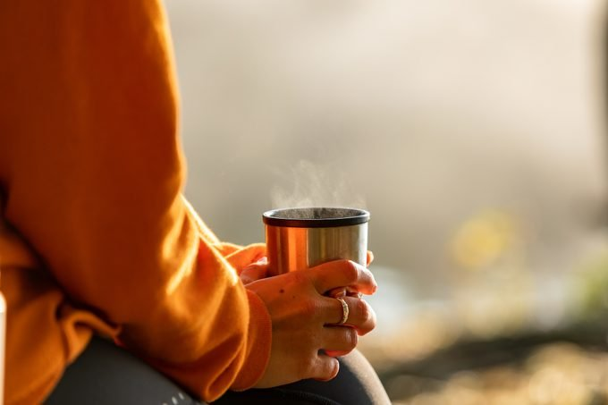 close up of person holding hot drink during the fall time outside