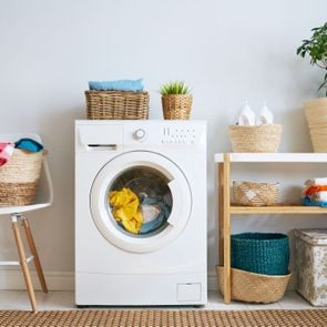 laundry room interior with clothes washer, laundry baskets, detergent and plant