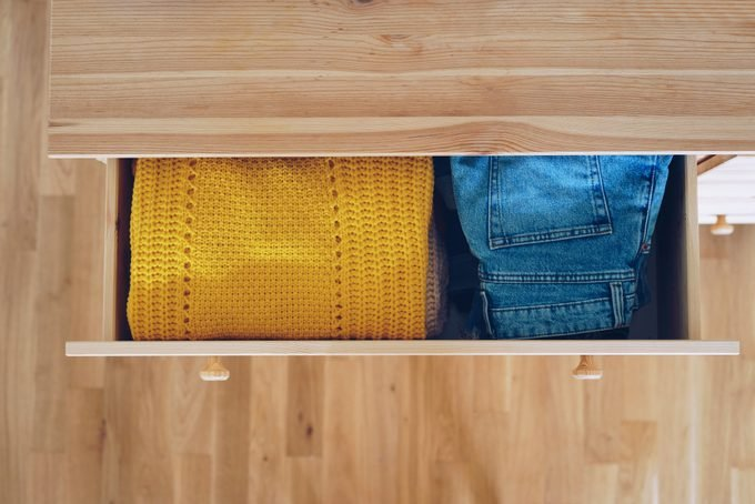 overhead view of neatly folded clothes, yellow sweater next to jeans, in an open drawer