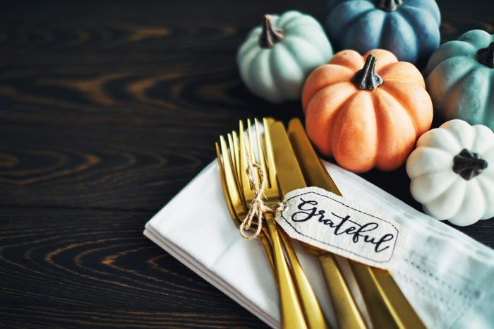 gold utensils with fall colored pumpkins on dining table