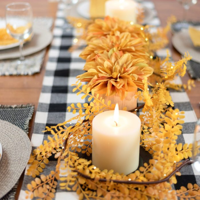 autumn dining table decorated with candles and gingham table runner