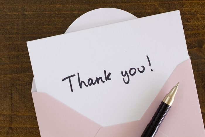 written Thank you card with pen on wood table