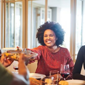 Smiling woman passing food to friend at thanksgiving party
