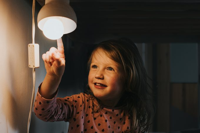 Little girl pointing at a Light bulb in home