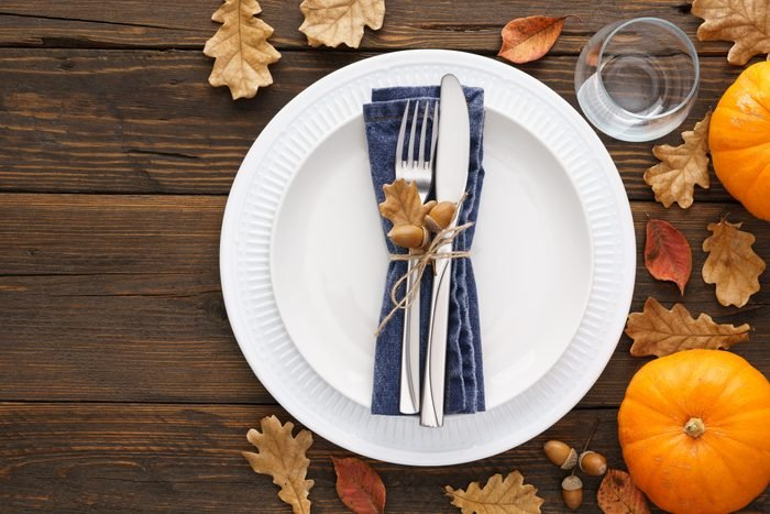 Thanksgiving Day table setting with leaves and pumpkins.