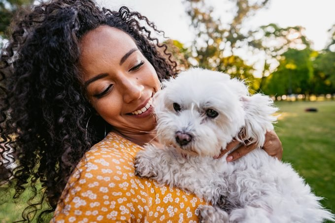 young woman holding her maltese dog in the park