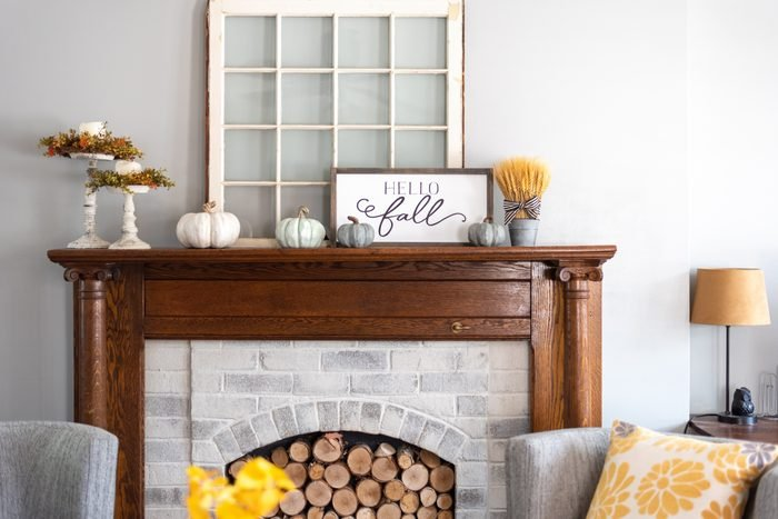 Stylish fall home decorations on a mantel in a living room