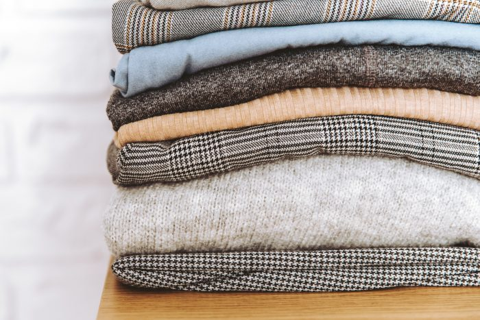 Stack of neatly folded clothes of wool, cotton, linen, silk, polyester on wood surface with white wall background