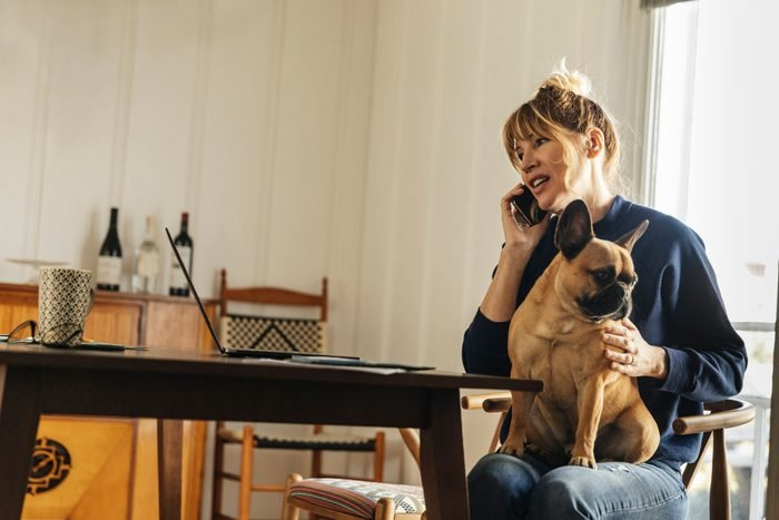 woman talking on the phone with dog in her lap at home