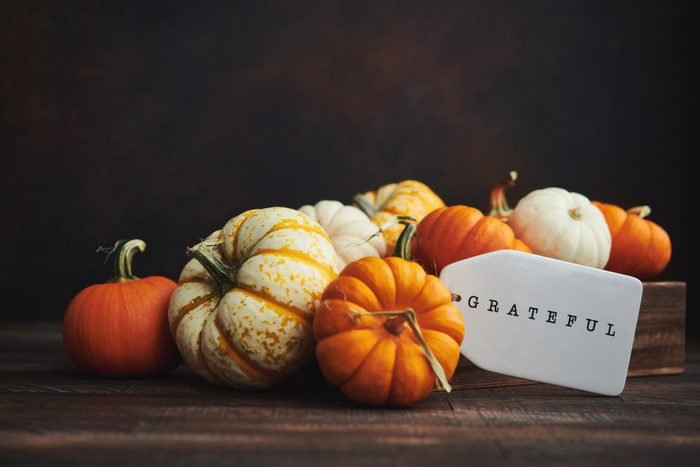 Collection of miniature pumpkins in wooden crate with GRATEFUL message for Fall and Thanksgiving