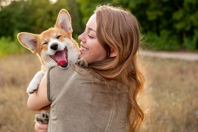 young woman with holding her corgi in a field