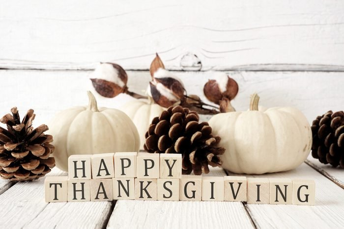 Happy Thanksgiving greeting against white wood with white pumpkins and brown autumn decor