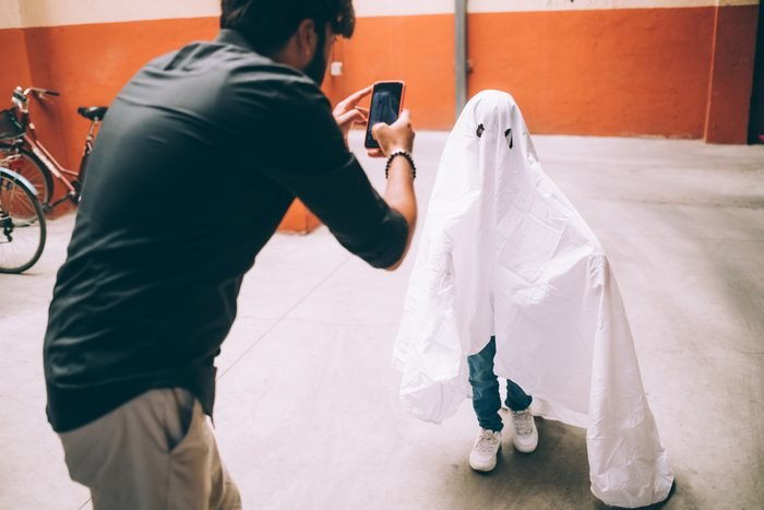 Father photographing child dressed as ghost