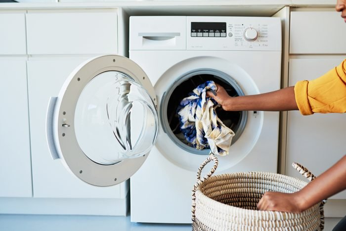 woman taking clothing out of a washing machine