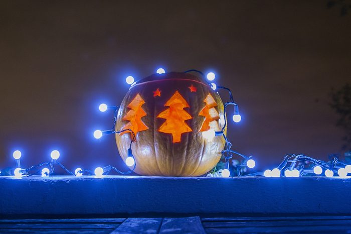 Jacko lantern decorated with blue Christmas lights glowing outdoors at night