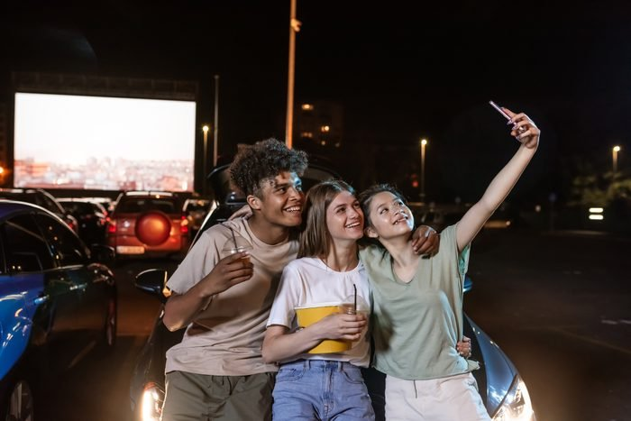 teenagers taking a selfie while at a drive in movie
