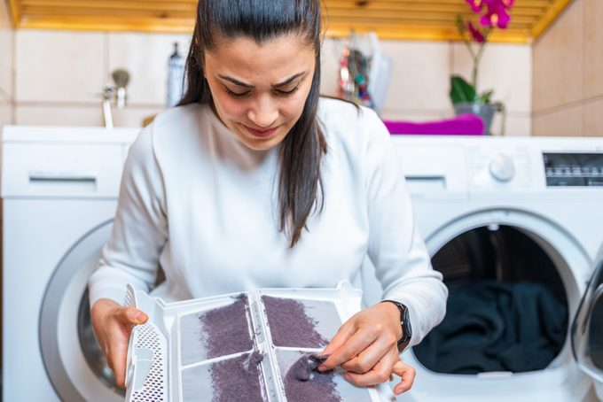 Young woman is removing lint from fluff dust filter of the tumble dryer. Dust and dirt trapped by the clothes dryer filter. Laundry processes