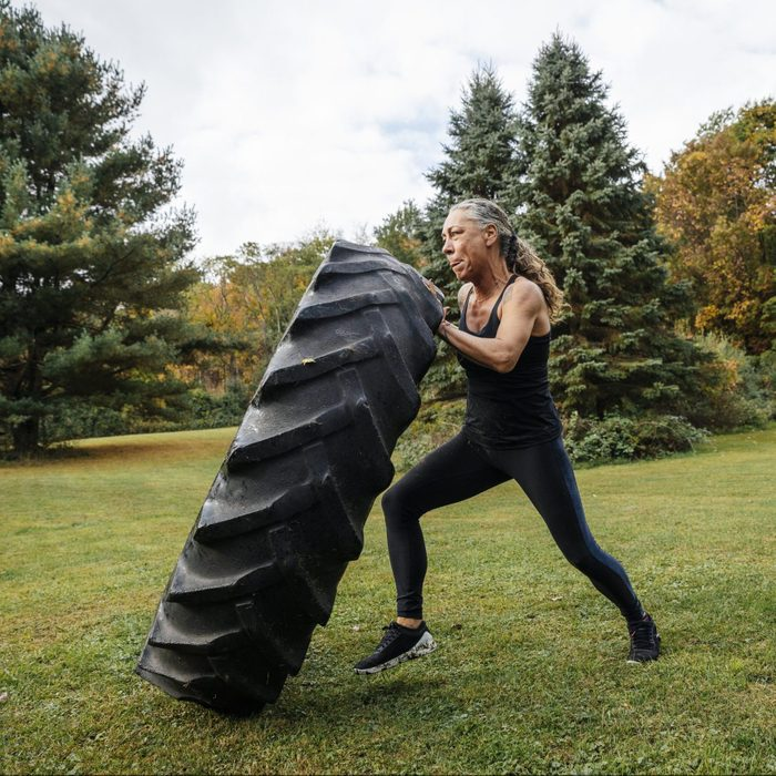 Strong Woman Pushing Tire While Exercising In Backyard