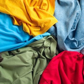 Lots of bright dirty colorful scattered clothes, abstract background. The concept of homework, lack of time for household chores.