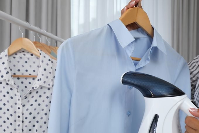 Woman steaming shirt on hanger at home