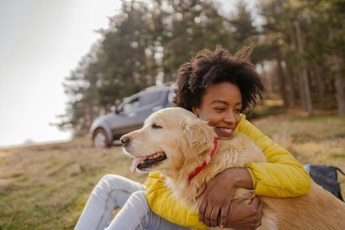 young woman hugging her golden retriever dog