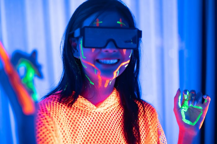Active teen girl playing game in vr headset, having fun in virtual reality world