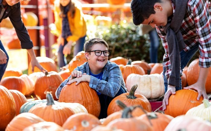 Boy with down syndrome having fun in pumpkin patch, smiling