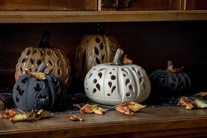 ceramic halloween pumpkins on wood shelf